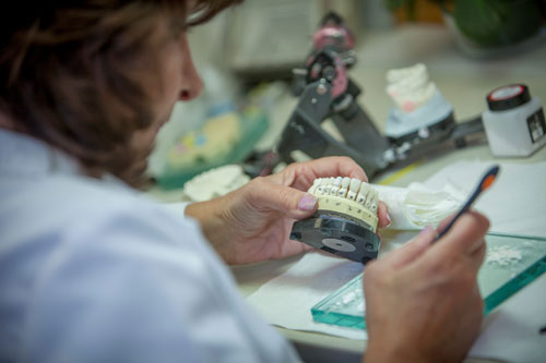 Over shoulder view of a dental professional working in dental lab at  Bay Lakes Center for Complex Dentistry